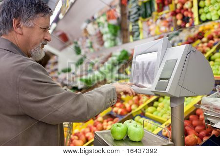 Handsome senior man shopping for fresh fruit in a supermarket (shallow DOF, sharp focus on the apples; color toned image)