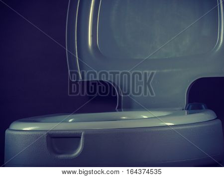 Open portable toilet bowl on gray background