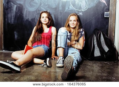 back to school after summer vacations, two teen real girls in classroom with blackboard painted together, lifestyle people concept