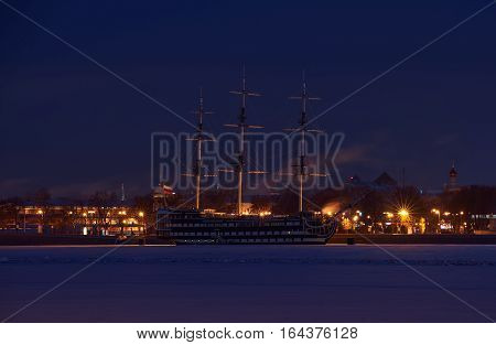 Old wooden ship near bank of Saint-Petersburg in winter night time.
