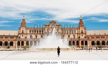 Spain Square is landmark in Seville, Andalusia, Spain. Plaza de Espana. Renaissance Revival style. Woman walking near Fountain