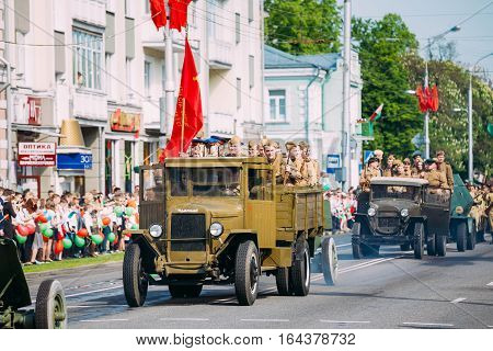 Gomel, Belarus - May 9, 2016: The Parade Of Russian Soviet Military Cars Of WW2 Time With Re-Enactors Dressed As Soldiers. The Truck ZIS-5V With Red Flag Foreground. Celebrating Victory Day Holiday