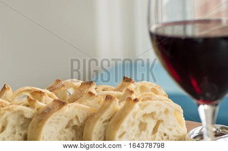 Freshly sliced bread on table with red wine selective focus on bread for food pairing or romantic details healthy lifestyle of simplicity and elegance