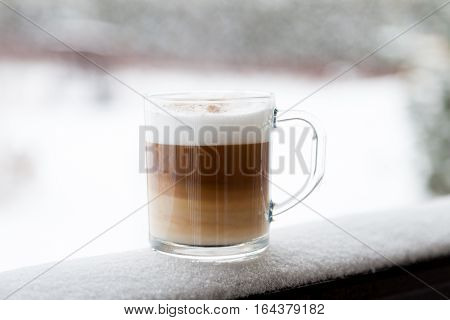 Cup with cappuccino coffee on the wooden bench covered with snow. Blurred winter background with snowflakes.