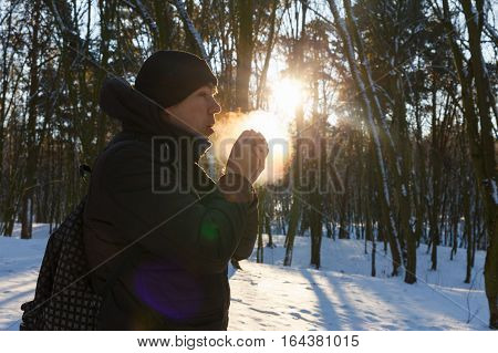 Young man warming up hands in snow covered forest