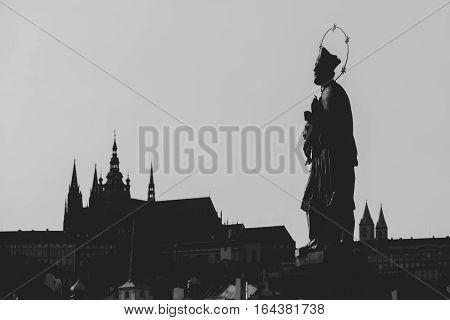 Statue of John of Nepomuk silhouette at Charles Bridge. Prague Czech Republic