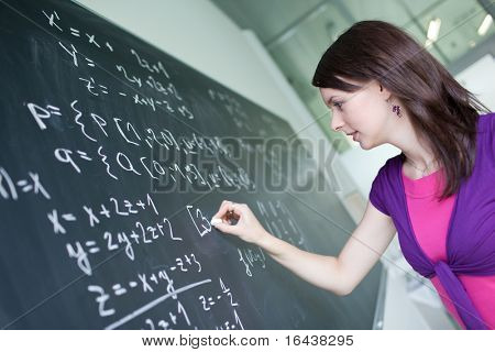pretty young college student or teacher writing on the chalkboard/blackboard during a math class (shallow DOF; color toned image)