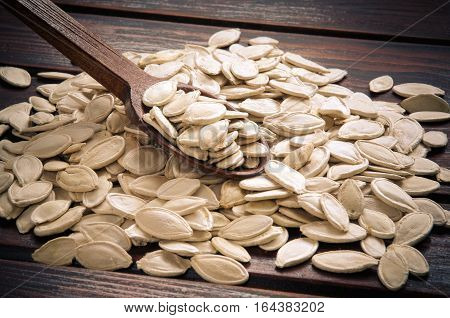Pumpkin seeds with wooden spoon on a wooden board.