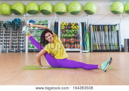 Attractive young brunette female athlete doing advanced split stretching exercise for legs smiling looking at camera while sitting on floor indoors in gym.