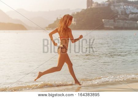 Back view of fit slim girl running barefoot on seashore wearing bikini. Young woman doing cardio exercise on beach lit in sunshine and city and mountains in background