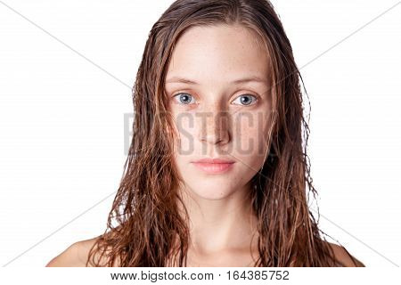Portrait of a beautiful model with wet hair and clean skin and freckles after shower isolated on white background.