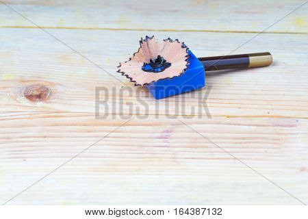 Pencil sharpener shavings on a wooden table. Back to school. Copy space.