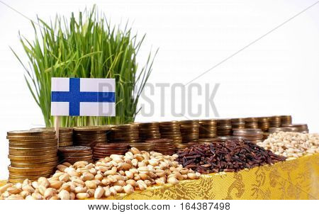 Finland Flag Waving With Stack Of Money Coins And Piles Of Wheat And Rice Seeds