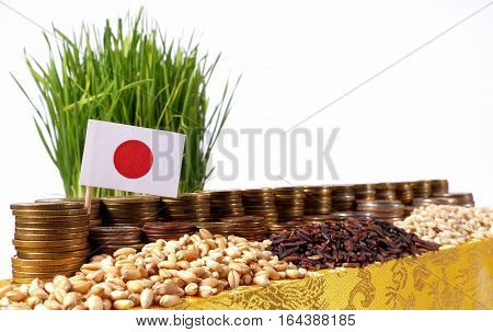 Japan Flag Waving With Stack Of Money Coins And Piles Of Wheat And Rice Seeds