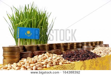 Kazakhstan Flag Waving With Stack Of Money Coins And Piles Of Wheat And Rice Seeds