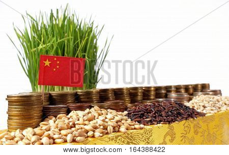 People's Republic Of China Flag Waving With Stack Of Money Coins And Piles Of Wheat And Rice Seeds