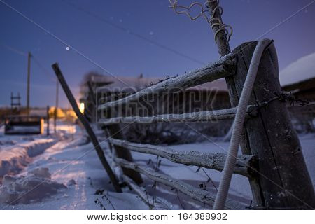 Rural fence covered with brilliant hoarfrost in the winter starlit night.