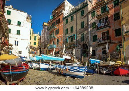 Colorful sailing boats at coast of Riomaggiore town at Cinque Terre National park, Italy