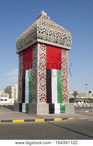 Tower decorated with the United Arab Emirates national flag in Sharjah UAE