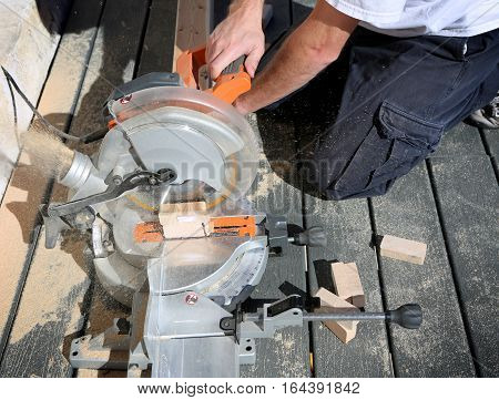 Carpenter using a circular saw to cut board of wood