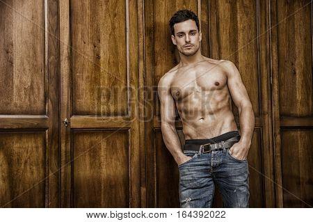 Sexy handsome young man standing shirtless in his bedroom against wooden wardrobe door
