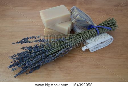 Four bars of goats milk soap on a light wooden table with a bouquet of dried lavender and a folded ramie washcloth. One bar of soap has lavender swirls. Natural light and shallow depth of field.