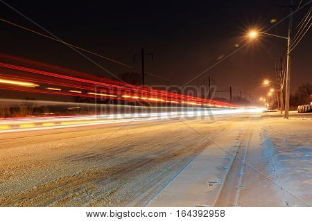 Snow covered winter road with shining streetlights in rural areas at sunset winter night snow covered roads with snow
