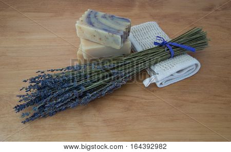 Three bars of handmade milk soap on a light wooden table with a bouquet of dried lavender and a folded ramie washcloth. Natural light and shallow depth of field.