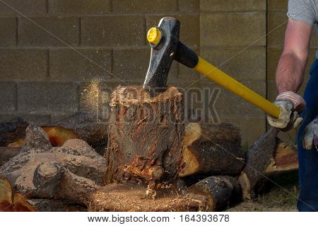 A piece of a log flies up after getting hit by an axe. The axe is stuck in the top of the log and the hands of the man who struck it are slipping off the axe handle. Sawdust is flying.