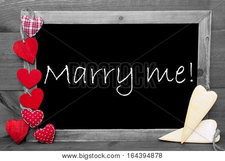 Chalkboard With English Text Marry Me. Red Hearts. Wooden Background With Vintage, Rustic Or Retro Style. Black And White Image With Colored Hot Spots.