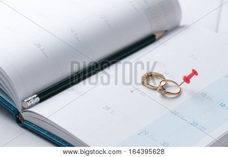 Wedding Gold Rings On Calender With Pencil.