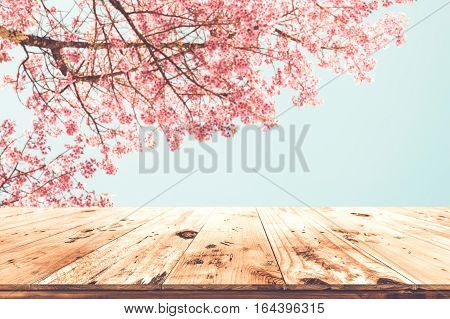 Top of wood empty ready for your product and food display or montage with pink cherry blossom flower (sakura) on sky background in spring season. vintage color tone.