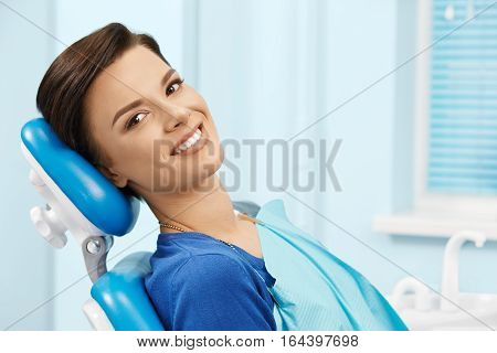 Young female patient visiting dentist office.Beautiful smiling woman with healthy straight white teeth sitting at dental chair.Dental clinic.Stomatology
