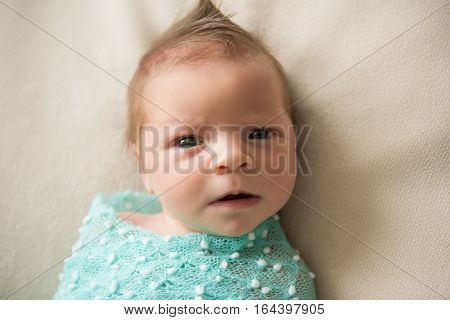 Newborn baby lies on a blanket with hairstyle Mohawk