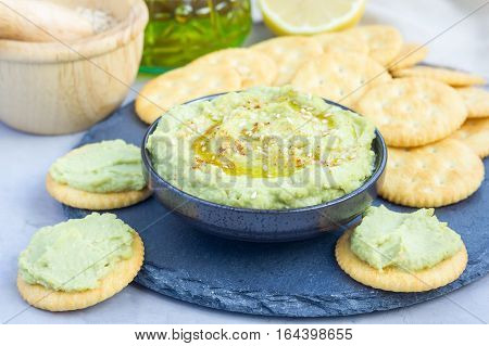 Healthy avocado hummus sprinkled with olive oil paprika and sesame served with crackers horizontal