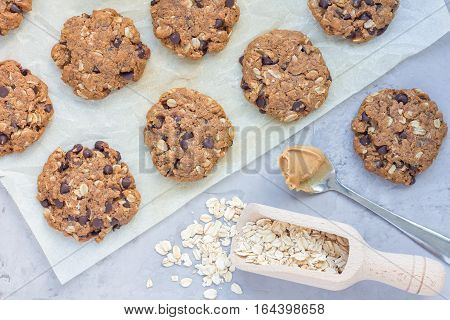Flourless gluten free peanut butter oatmeal and chocolate chips cookies on parchment top view horizontal