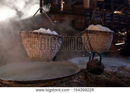 Boiling rock salt , Lapping crystallized salt from boiled saltwater to dried up the basket. Nan ,Thailand.