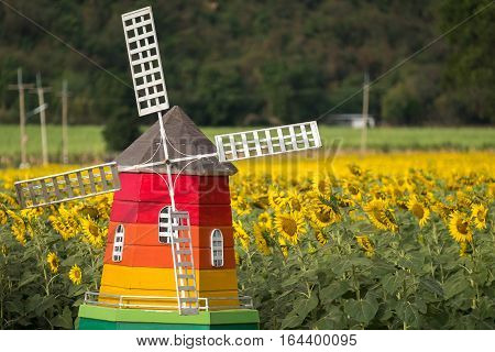 Decorative old wind mill in sunflower field