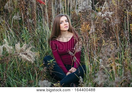Portrait of pensive sad lonely Caucasian blonde young beautiful woman girl with long hair wearing jeans red shirt sitting in forest field among plants grass looking in camera autumn summer
