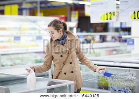 pretty young buying frozen fish/groceries in a supermarket/mall/grocery store (color toned image; shallow DOF)