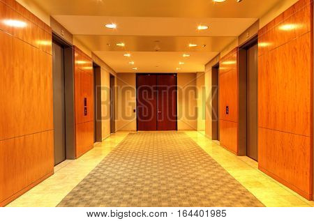 Polished, high end up and down elevator hallway in a corporate business building.