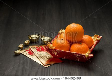 Chinese New Year,golden Envelope Packet (ang Pow) With Gold Ingots And Oranges On Brown Wood Table T