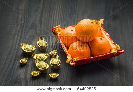 Chinese New Year,gold Ingots And Oranges On Brown Wood Table Top