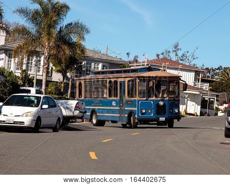 Laguna Beach, California, USA - January 8, 2017: Laguna Beach trolley drives along Cliff Drive near Diver's Cove in Laguna Beach, California in winter. Editorial use only