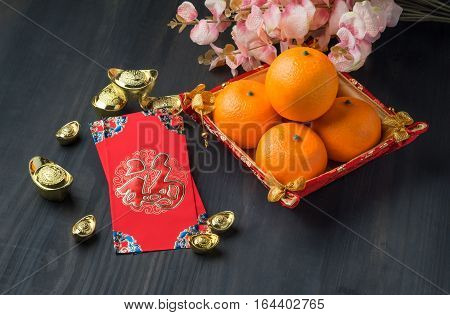 Chinese New Year,red Envelope Packet (ang Pow) With Gold Ingots And Oranges And Flower On Brown Wood
