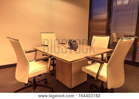 Small corporate conference room with a table and four chairs around a conference bridge phone in a professional building.