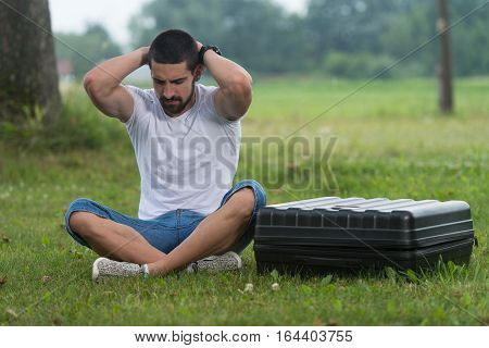 Sad Man Sitting On Grass With Case Drone
