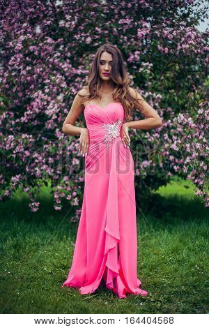 Portrait of young beautiful woman wearing long pink dress posing in spring blossom trees. Professional make-up and hairstyle. Perfect skin. Fashion photo.