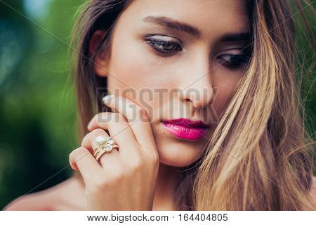 Portrait of beautiful girl with summer make-up. Stacking rings jewelry. Professional make-up and hairstyle. Perfect skin. Fashion photo.