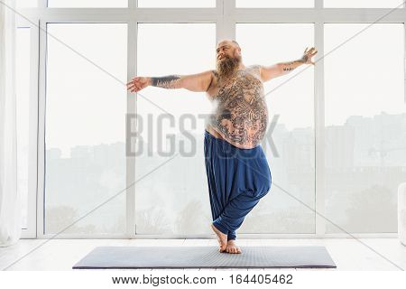 Graceful fat man is doing yoga with pleasure. He is stretching arms sideways and relaxing. Man is standing on mat and smiling